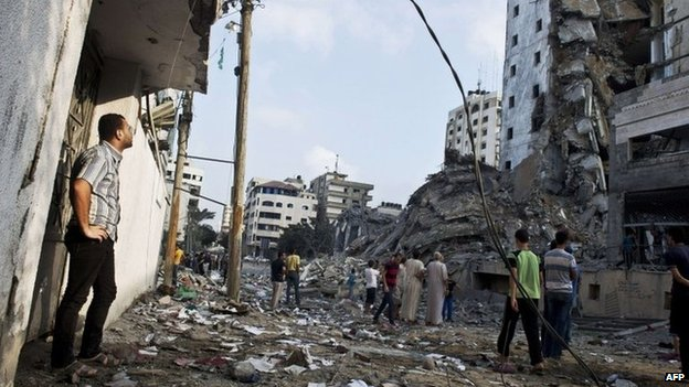 Palestinians look at a high-rise building in Gaza City that targeted in an Israeli air strike on 26 August 2014