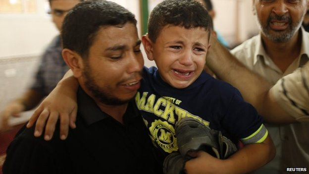 A Palestinian boy is comforted during the funeral for his father Mohammed Abu Ajwa, a Hamas militant, who was killed in an Israeli air strike (26 August 2014)