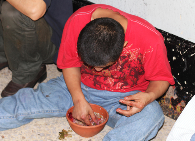 A man sits on the floor against the wall, eating out of a bowl