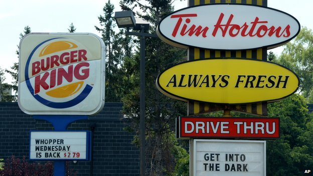 A Burger King sign stands next to one for Tim Hortons.