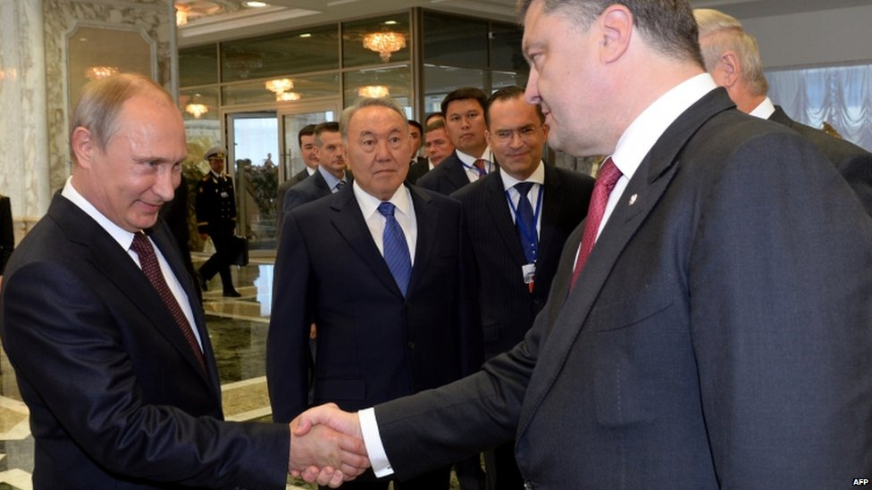 Russian President Vladimir Putin (left) and Ukrainian President Petro Poroshenko shake hands at a summit in Minsk, Belarus