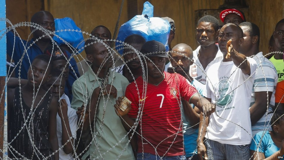 Liberian residents of the West Point slum react behind a wired fence around the quarantined area in the capital Monrovia