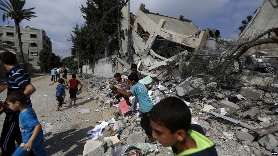 Palestinian children play on the wreckage of a building destroyed by Israeli air strikes in Gaza City