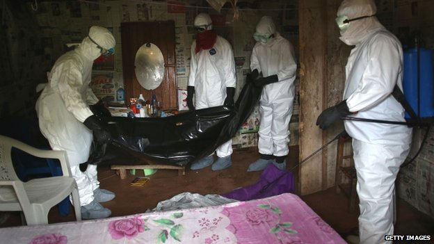 A team helps dispose of a person who died of Ebola in Liberia - August 2014