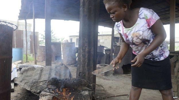 A woman roasts a fresh bushmeat, at the Ajegunle-Ikorodu market in Lagos, Nigeria - 13 August 2014