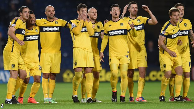 Oxford United's players watch on during the penalty shootout
