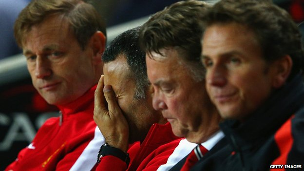 Manchester United assistant manager Ryan Giggs, centre-left, covers his face with a hand as he sits next to manager Louis van Gaal during the games against MK Dons