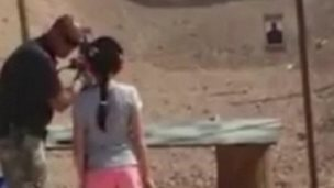 Instructor at Last Stop firing range showing nine-year-old girl how to fire Uzi