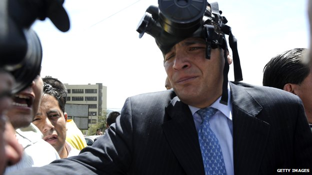 Ecuadorean President Rafael Correa, wearing a gas mask, talks with journalists at the Regimiento Quito barracks in Quito on 30 September , 2010.