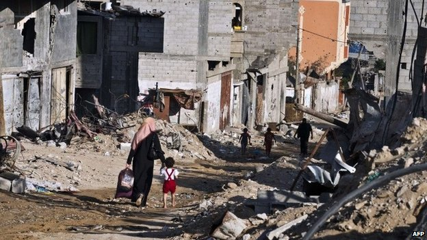 A woman and her child return to their home in Gaza City's Shejaiya district (27 August 2014)