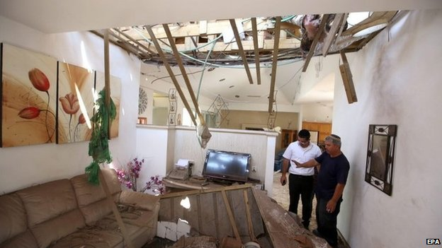 Israelis inspect damage to a house in the southern town of Ashkelon (26 August 2014)