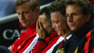 Ryan Giggs has his head in his hands, sat next to Louis van Gaal