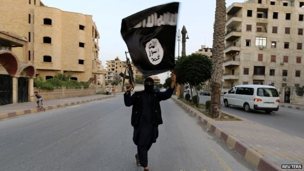 Militant waves Islamic State flag in Raqqa, Syria, in June 2014