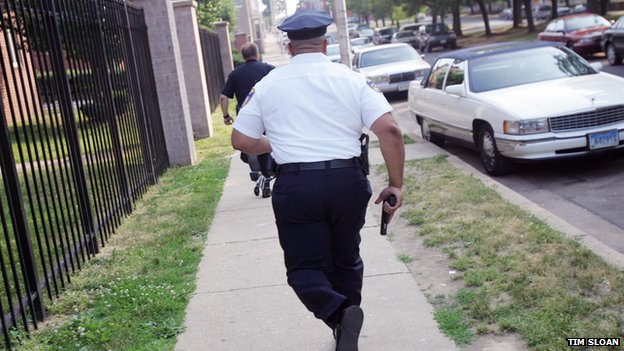 A Baltimore police officer runs with his gun drawn.