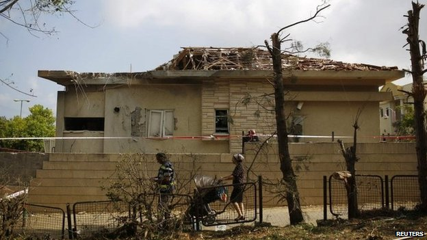 Israelis walk past a house damaged by a rocket in the southern Israeli town of Ashkelon (26 August 2014)