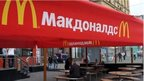 People sitting outside closed Moscow branch of McDonalds