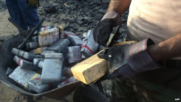 A man scrapes off coal from a brick of cocaine on 26 August 2014