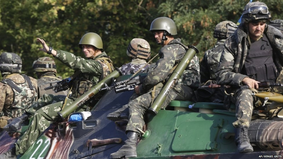 Ukrainian soldiers ride atop an APC near the village of Sakhanka, eastern Ukraine, on 27 August 2014.