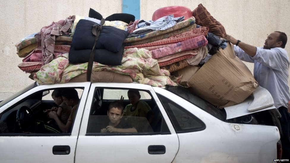 A Palestinian man and his family prepare to return home from the UN school in Gaza City on 27 August 2014