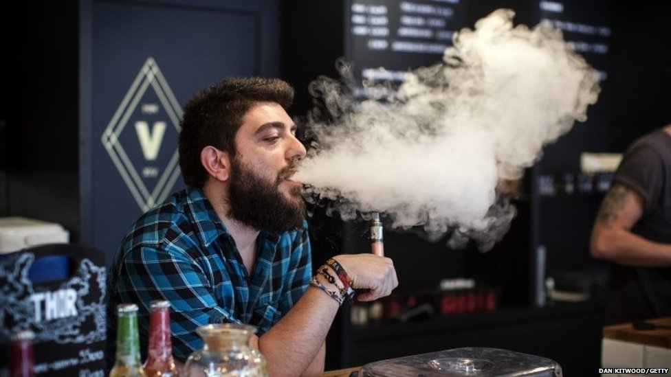 Vape Lab employee Leonardo Verzaro uses an e-cigarette while working on 27 August 2014 in London, England.