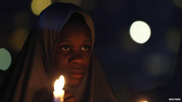 "A campaigner of ""#Bring Back Our Girls"" holds candles during a candlelight vigil for Ameyo Stella Adadevoh and other Ebola victims in Abuja August 26, 2014. Adadevoh, a consultant physician and endocrinologist, died after contracting the deadly Ebola virus while treating a Liberian-American, Patrick Sawyer, and other victims of the disease in Nigeria."