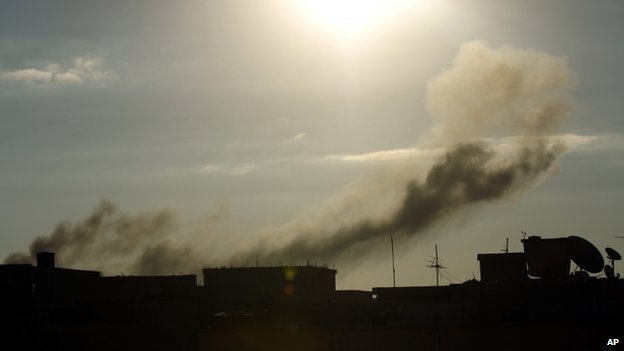 Smoke rises from buildings following an air strike attack early in the morning on 27 August, 2014, near military camps in Libya's eastern coastal city of Benghazi.