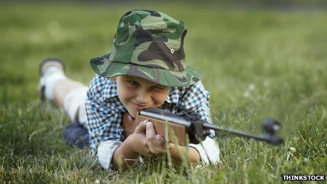 A young boy holds a rifle