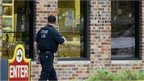 """A crime lab technician walks past bullet riddled windows at a Wendy""""s in Omaha, Neb., Wednesday, Aug. 27, 2014"""