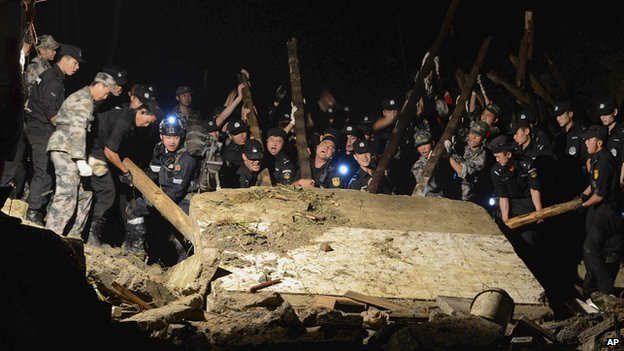 Rescue workers lift a wall that collapsed after a landslide hit Yingping village in Fuquan city in southwest China's Guizhou province on Thursday 28 August, 2014
