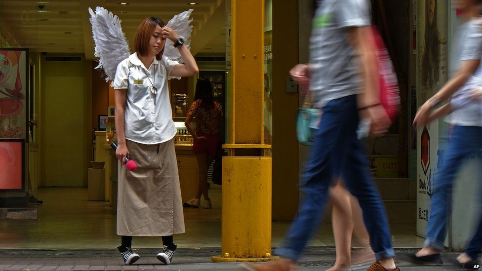 An employee wearing a pair of wings waits for her shift to end at Ximendin fashion district in Taipei, Taiwan