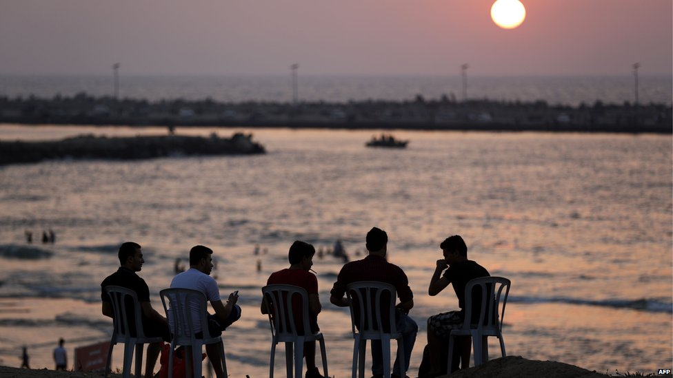 Palestinian youths sit on the beach in Gaza City during sunset after a truce was agreed between Israel and Hamas