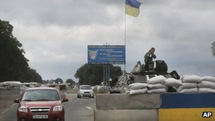 Ukrainian forces guard a checkpoint in Mariupol