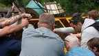 People at the adventure park try to get the tipped train back on its wheels