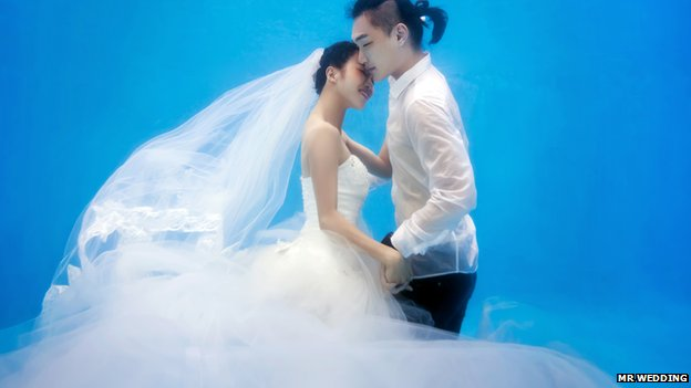 A bride and groom embracing underwater