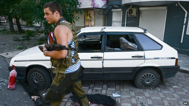 Pro-Russian rebel passes damaged car in Donetsk (27 August 2014)