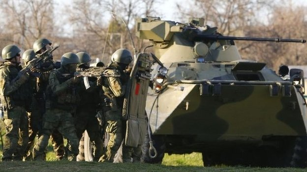 Armed men, believed to be Russian servicemen, are positioned behind an armoured vehicle near a military airbase in the Crimean town of Belbek near Sevastopol on 22 March 2014.
