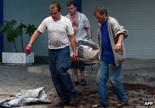 Men remove a shell victim in Donetsk, 28 August