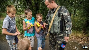 Children examine a machinegun of a Ukrainian serviceman patrolling in the small city of Dzerzhynsk, Donetsk region, 28 August 2014