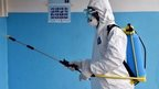 A man wearing a protective suit washes a health centre's walls in the Ivory Coast - 14 August 2014