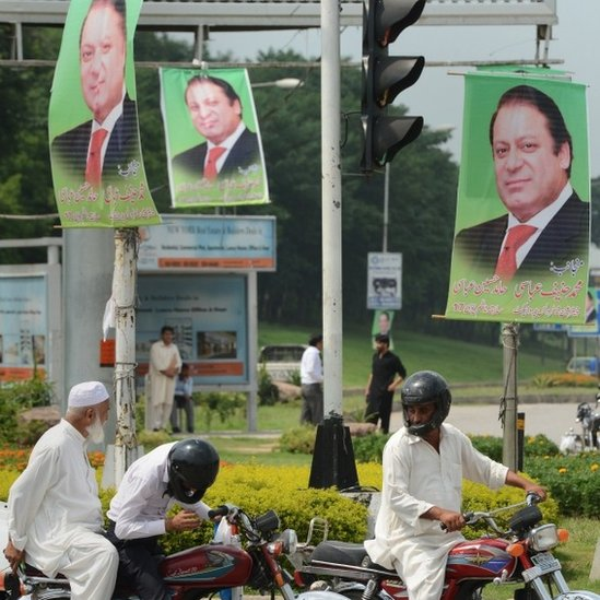 Pakistani commuters wait at the traffic lights alongside a poster of Prime Minister Nawaz Sharif on a highway in Islamabad on August 25, 2014.
