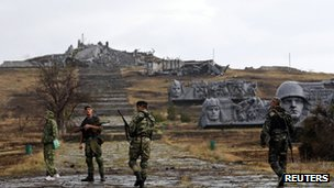 Russian separatists near a damaged war memorial at Savur-Mohyla, a hill east of the city of Donetsk.
