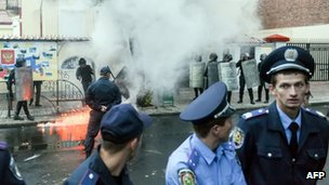 Ukrainian police standing near a smoke bomb as smoke pours out
