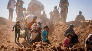 Hundreds of Syrian refugees stream across the border into Jordan at a remote border point in the east