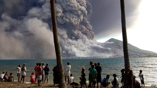 A file photo taken on 7 October, 2006, shows evacuated Matapit Islanders watching Mt Tavurvur volcano erupt sending ash and rocks over the already devastated city of Rabaul on New Britain Island in Papua New Guinea