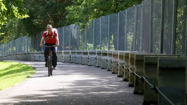 A man cycles past a security fence