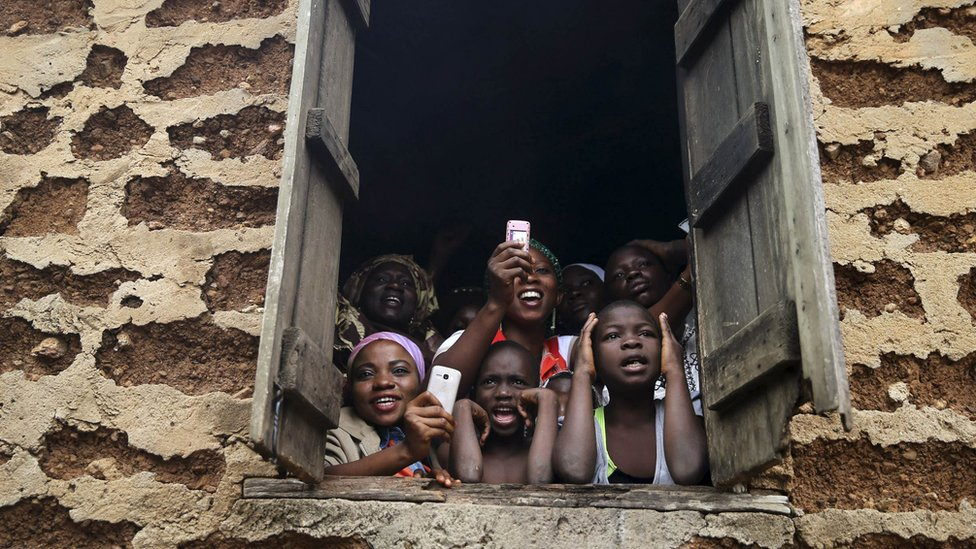 People in Osogbo in Osun state look out of a window at the those taking part in the Osun-Osogbo Sacred Grove Festival - Friday 22 August 2014