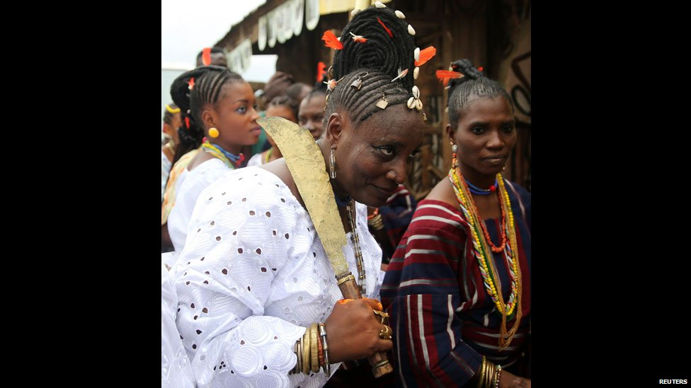 A woman in white with a traditional sword takes part in the  Osun-Osogbo Sacred Grove Festival procession in Osun state, Nigeria - Friday 22 August 2014