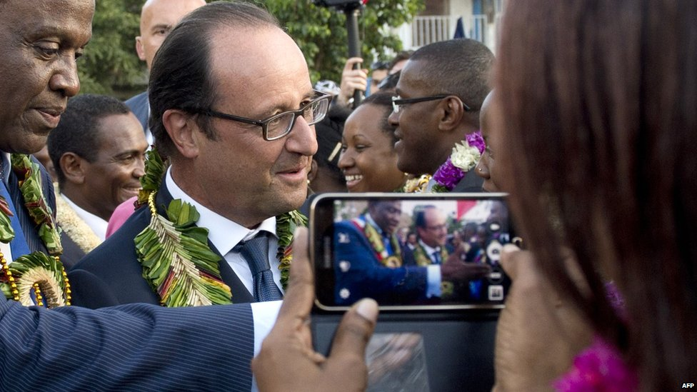 A woman films French President Francois Hollande on her mobile phone in Dzaoudzi on Mayotte - a French island territory - Friday 22 August 2014