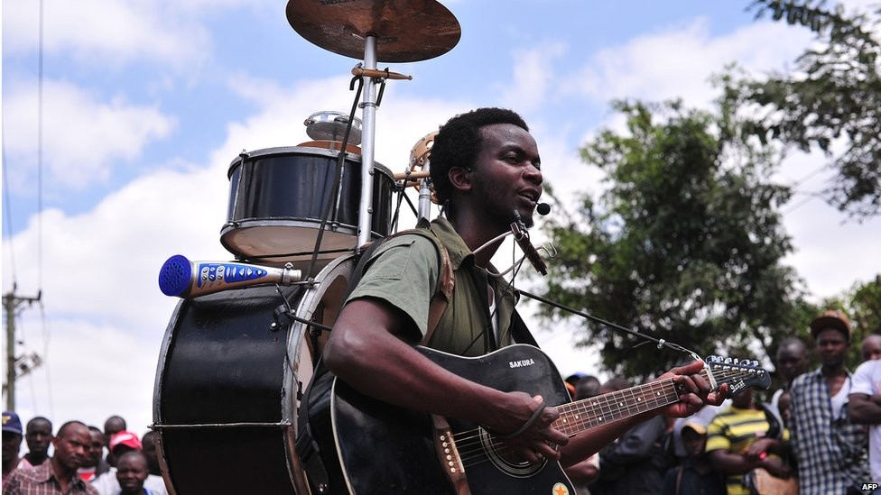 "One-man band Joshua Kamau, known as ""Krack Wizz"", entertains onlookers at  Kagemi market on the outskirts of Nairobi, Kenya - Wednesday 27 August 2014"