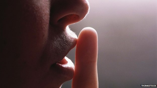 A person with their finger to their lips